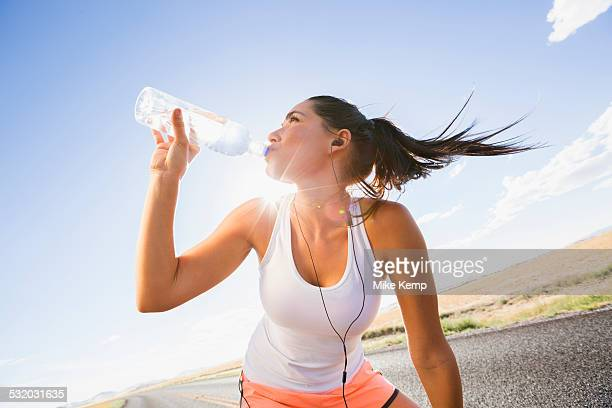 Caucasian runner drinking water bottle on remote road