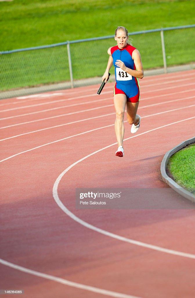 Caucasian runner holding baton running on track : Stock Photo