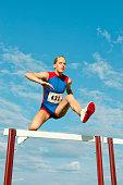 Caucasian runner jumping over hurdles on track