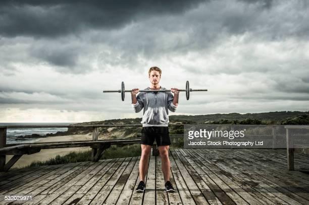 Caucasian runner lifting weights on wooden boardwalk at beach