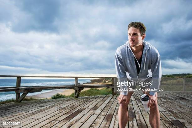Caucasian runner resting on wooden boardwalk at beach