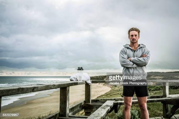 Caucasian runner standing on wooden boardwalk at beach
