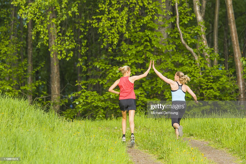 Caucasian runners high fiving on path
