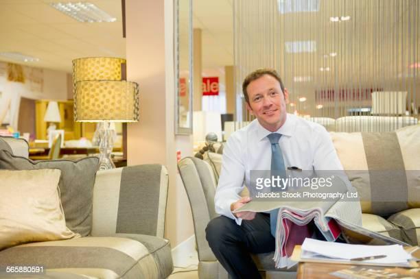 Caucasian salesman examining fabric swatches in furniture store
