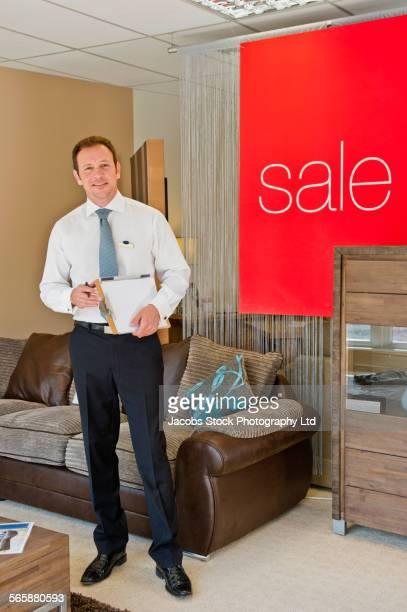 Caucasian salesman smiling in furniture store