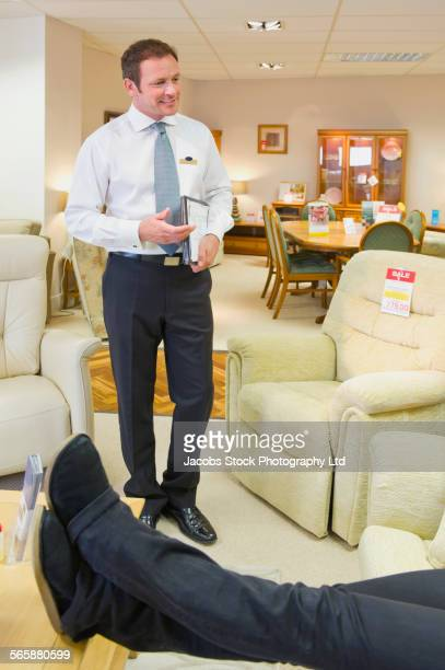 Caucasian salesman talking to customer in furniture store