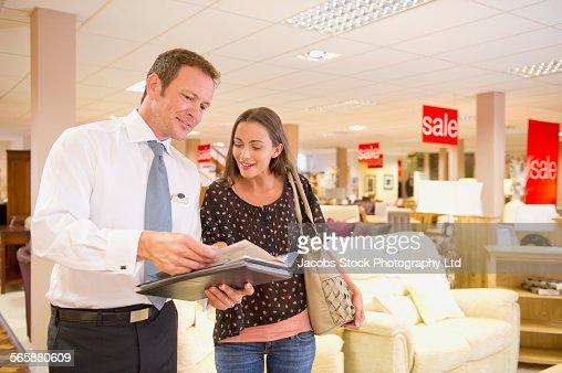 Caucasian salesman talking to customer in furniture store : Stock Photo