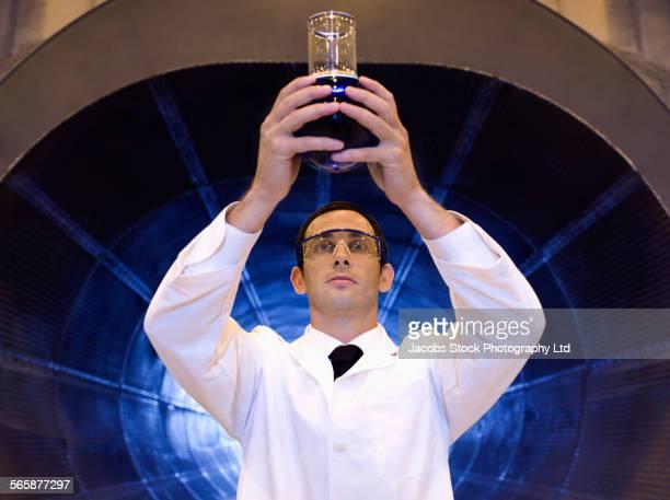 Caucasian scientist examining chemicals in tunnel