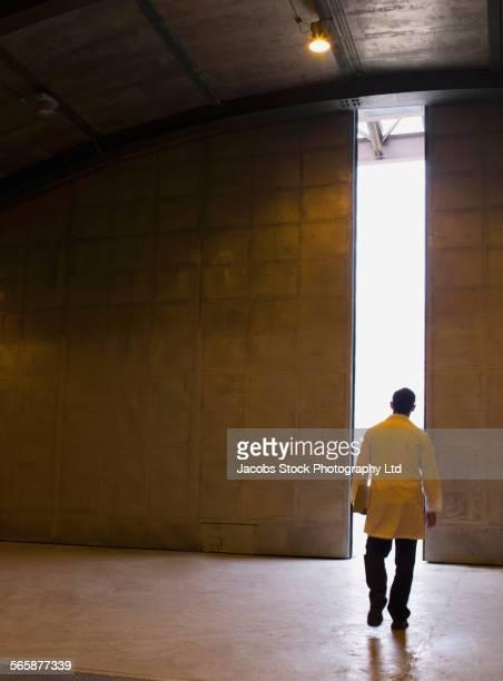 Caucasian scientist walking to light from doorway