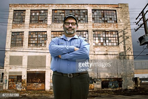 Caucasian security guard outside dilapidated building