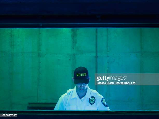 Caucasian security guard sitting in control room
