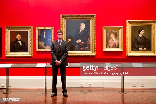 Caucasian security guard standing in art museum