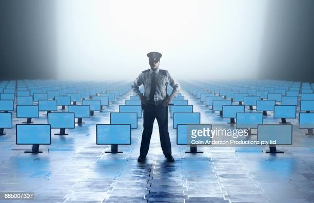 Caucasian security guard watching with abundance of computer monitors