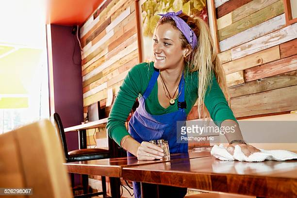 Caucasian server wiping down tables in cafe