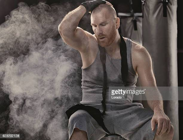 Caucasian shaved male adult boxer sitting alone exhausted after workout