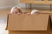 Caucasian sisters playing in cardboard box