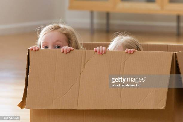 Caucasian sisters playing in cardboard box