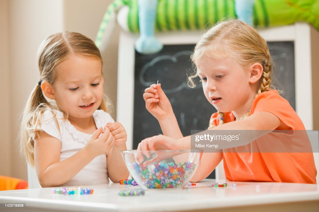 Caucasian sisters playing with beads