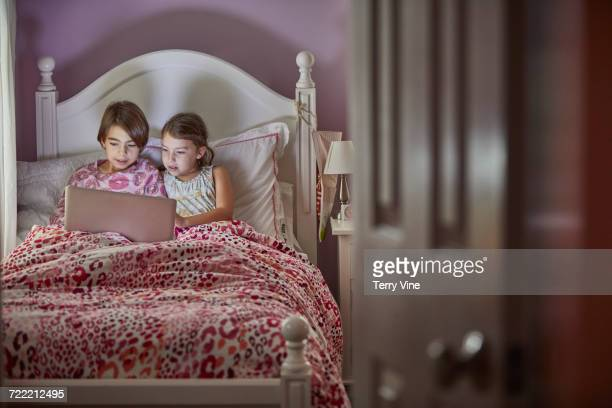 Caucasian sisters sitting in bed using laptop