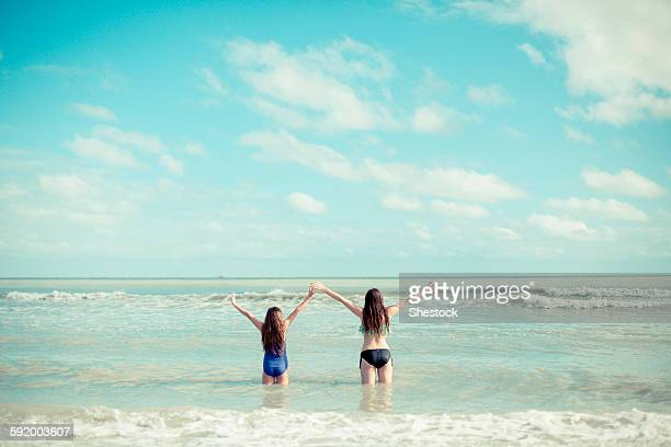 Caucasian sisters standing in waves on beach