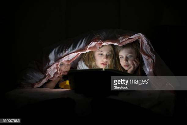 Caucasian sisters using laptop in blanket fort night