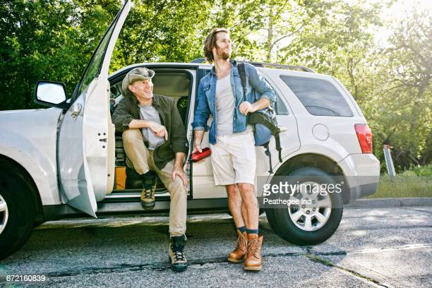 Caucasian sitting and standing at car