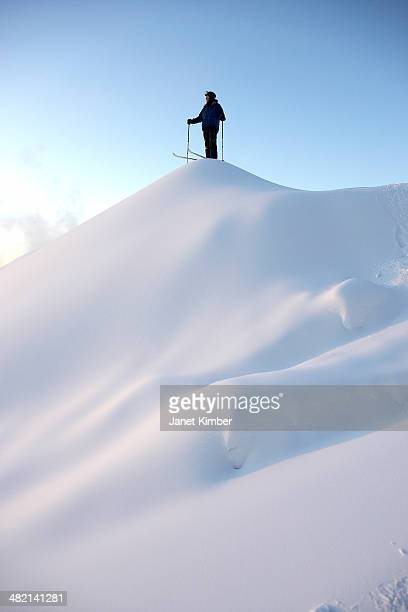 Caucasian skier standing on snowy hilltop