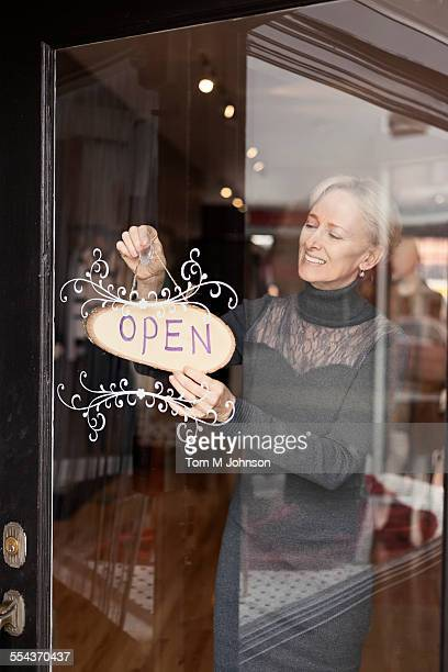 Caucasian small business owner hanging open sign on front door