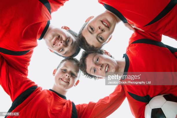 Caucasian soccer team putting heads together in huddle