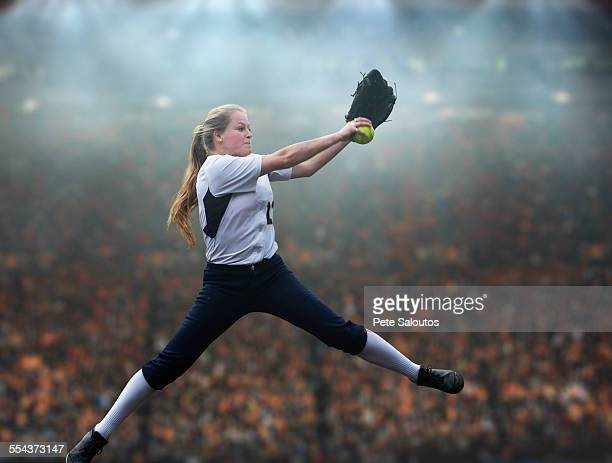 Caucasian softball player pitching ball in stadium