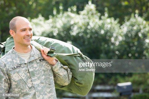 Caucasian soldier carrying duffel bag outdoors