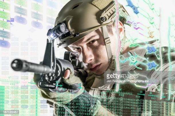 Caucasian soldier pointing gun at illuminated holograms