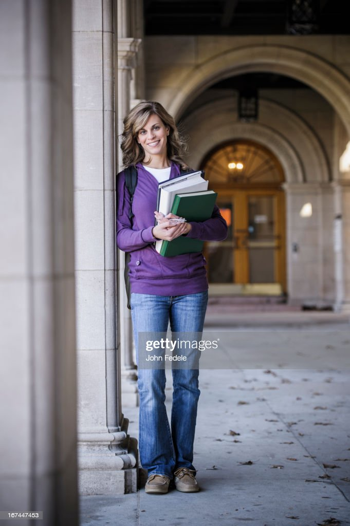Caucasian student carrying books on campus : Stock Photo
