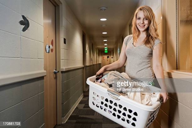 Caucasian student carrying laundry in dorm hallway