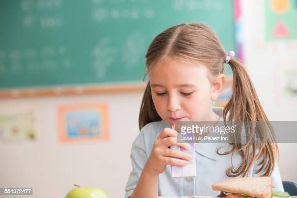 Caucasian student drinking juice box in classroom