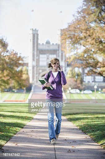 Caucasian student on cell phone on campus : Stock Photo
