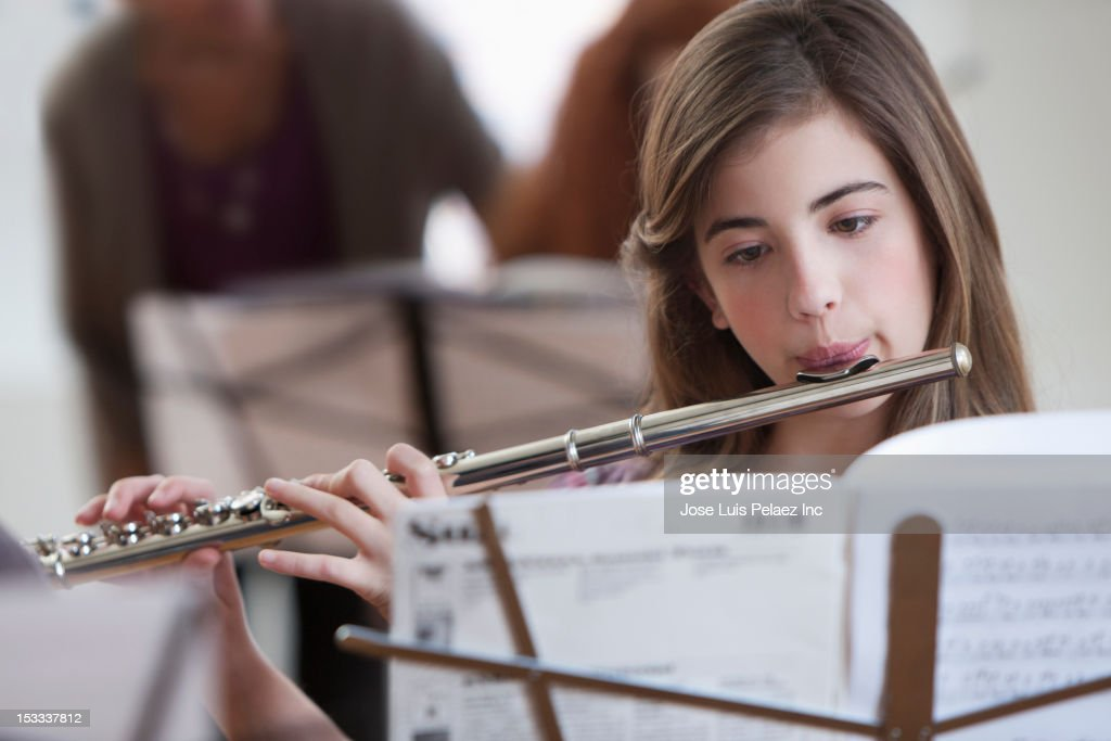 Caucasian student playing flute in music class : Stock Photo