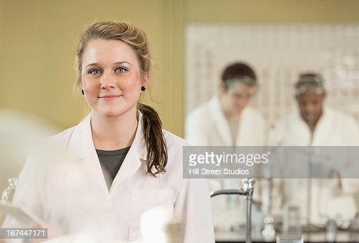 Caucasian student smiling in lab classroom : Stock Photo