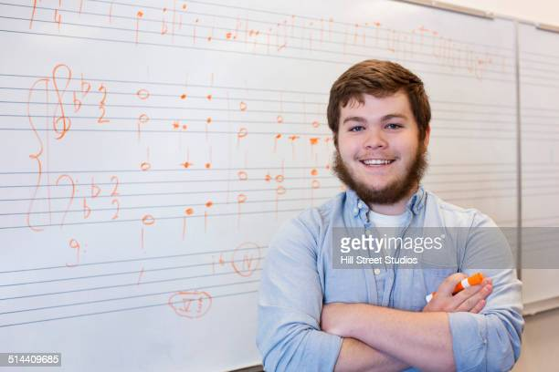 Caucasian student standing at board in music class
