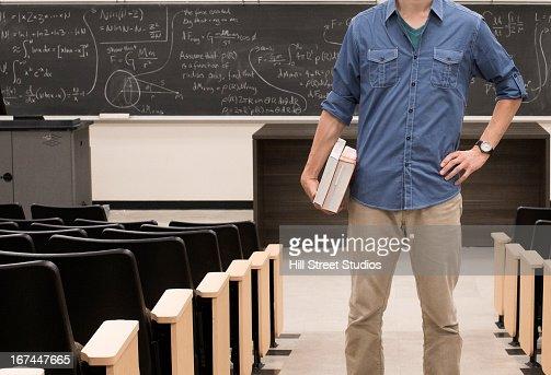 Caucasian student standing in classroom : Stock Photo