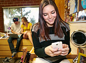 Caucasian student using cell phone in dorm room