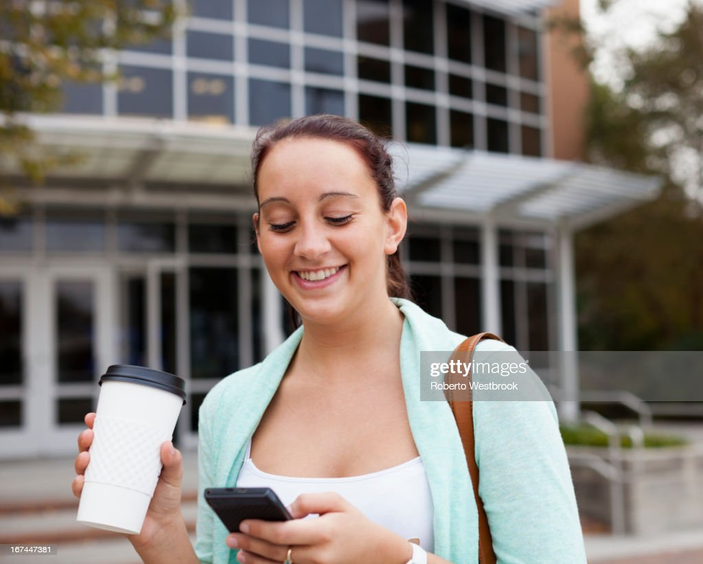Caucasian student using cell phone on campus : Stock Photo
