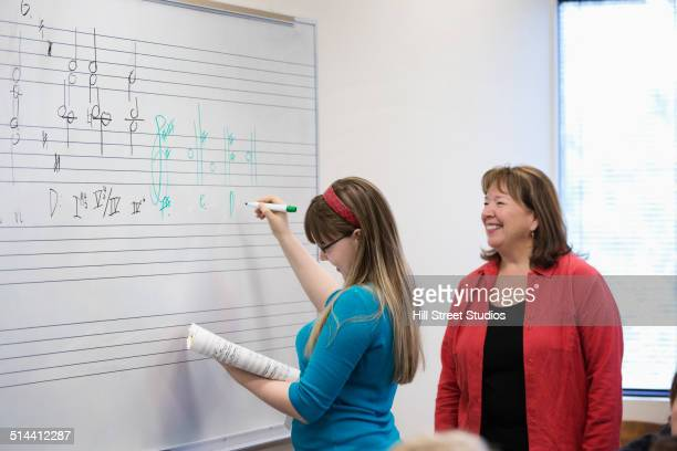 Caucasian student writing on board in music class