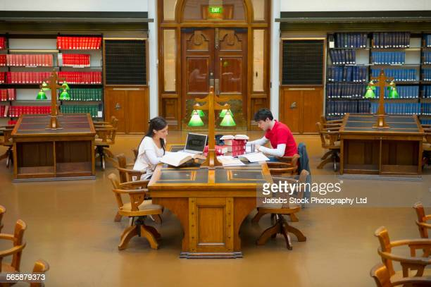 Caucasian students reading books in library