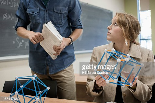 Caucasian students working in classroom : Stock Photo
