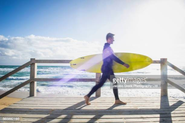 Caucasian surfer carrying surfboard on beach boardwalk
