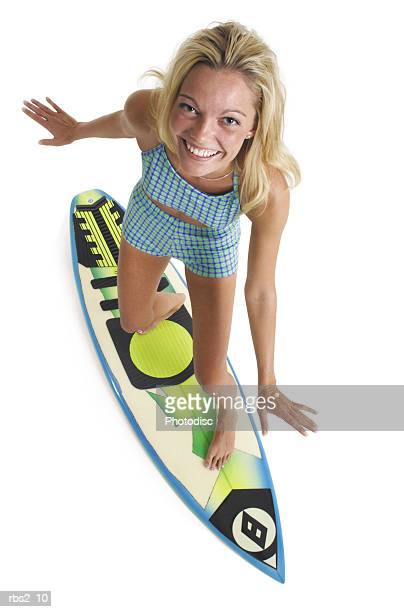 caucasian surfer girl in light blue swimsuit stands on surfboard smiles and looks up to the camera