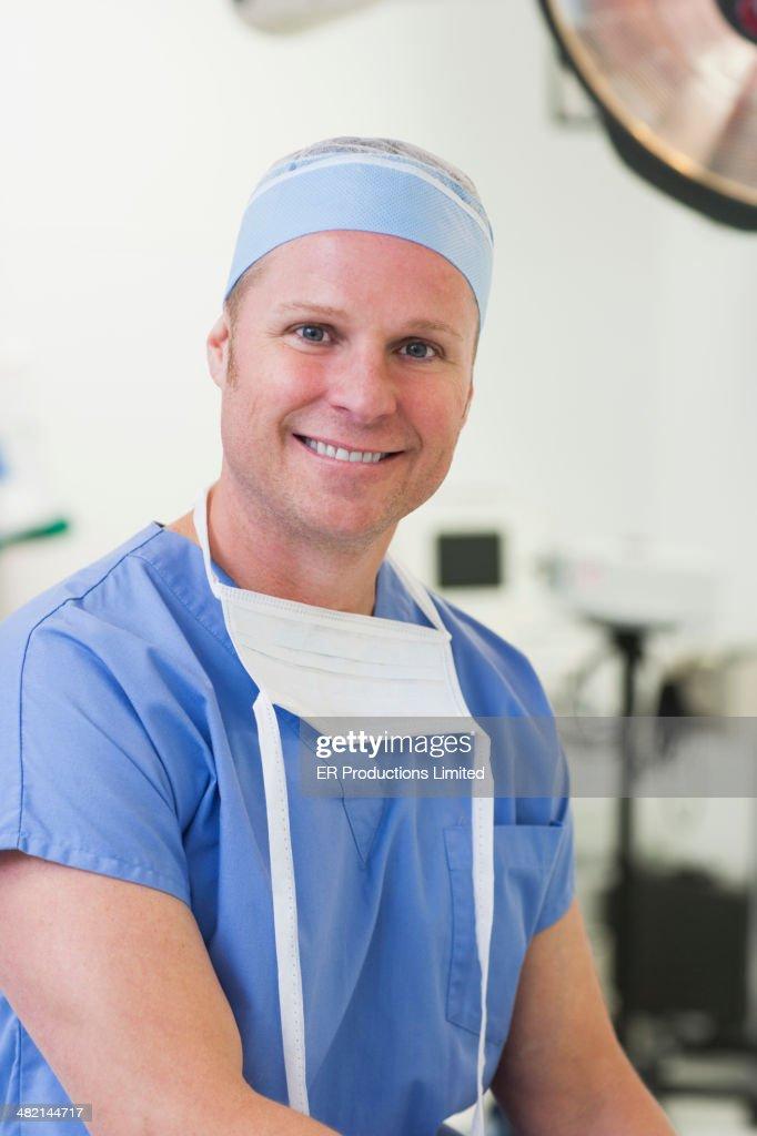 Caucasian surgeon smiling in operating room : Stock Photo