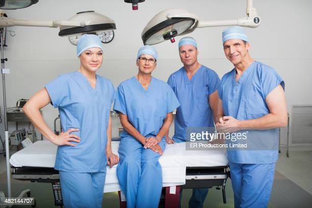Caucasian surgeons smiling in operating room