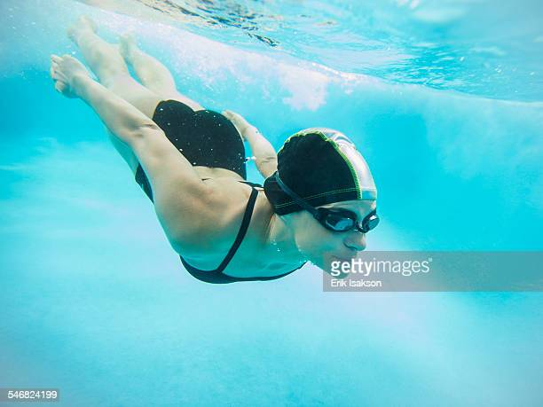 Caucasian swimmer diving into swimming pool